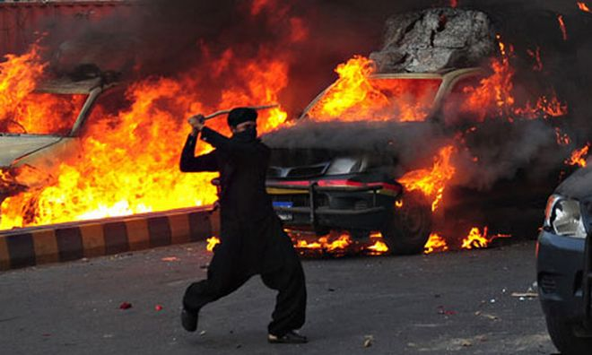 A Pakistani man brandishes a stick near burning vehicles during protests against the anti-Islam film
